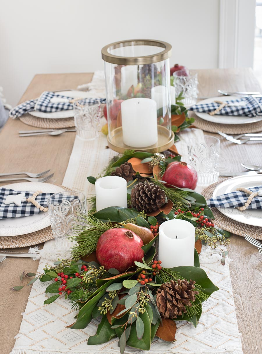 Gorgeous! This post gives you the step by step to making a live greenery table runner with magnolia leaves, greenery, fruit, and pinecones!