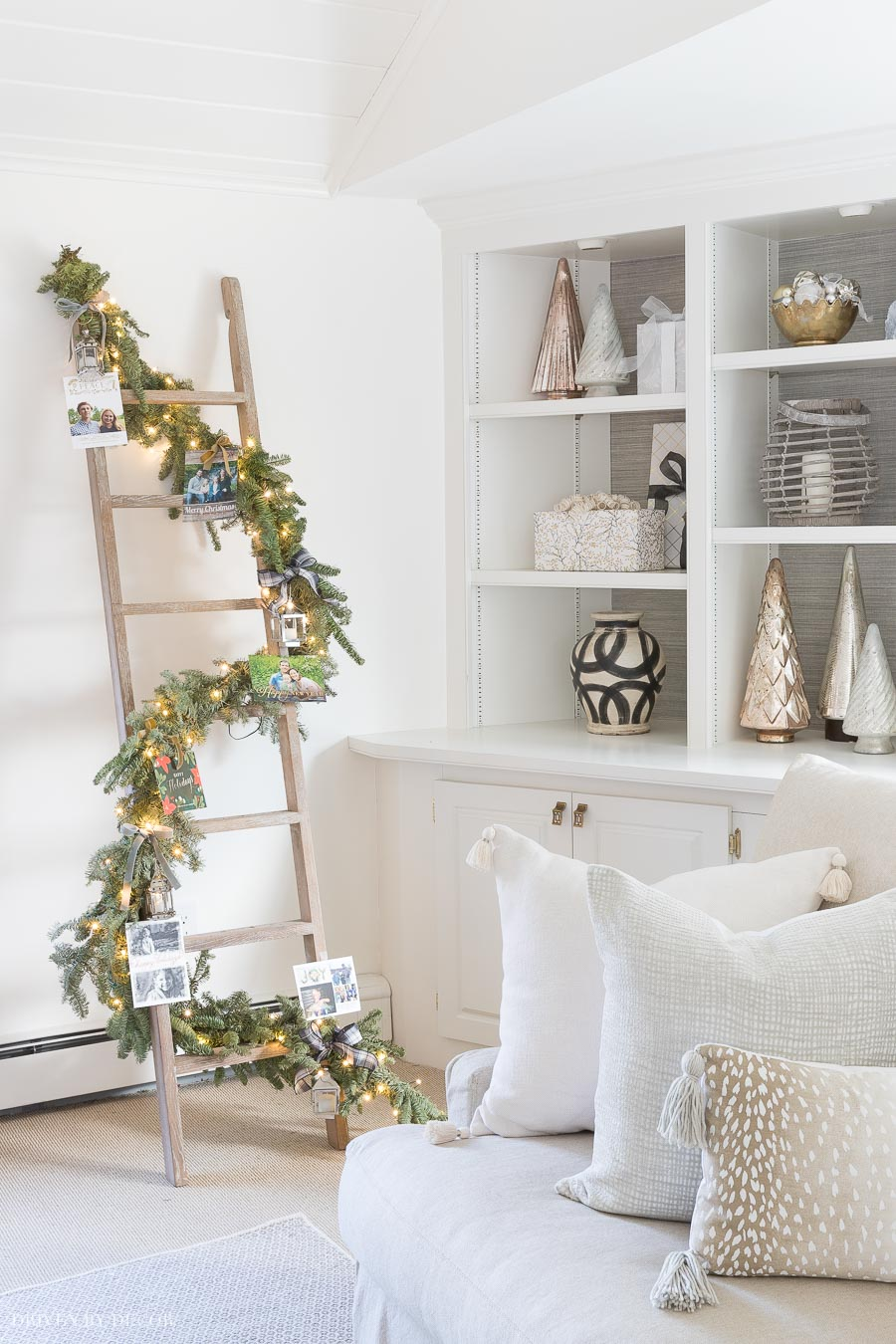 Wrap a garland and twinkle lights around a ladder and tie on Christmas cards for a beautiful, unique way to display your holiday cards!