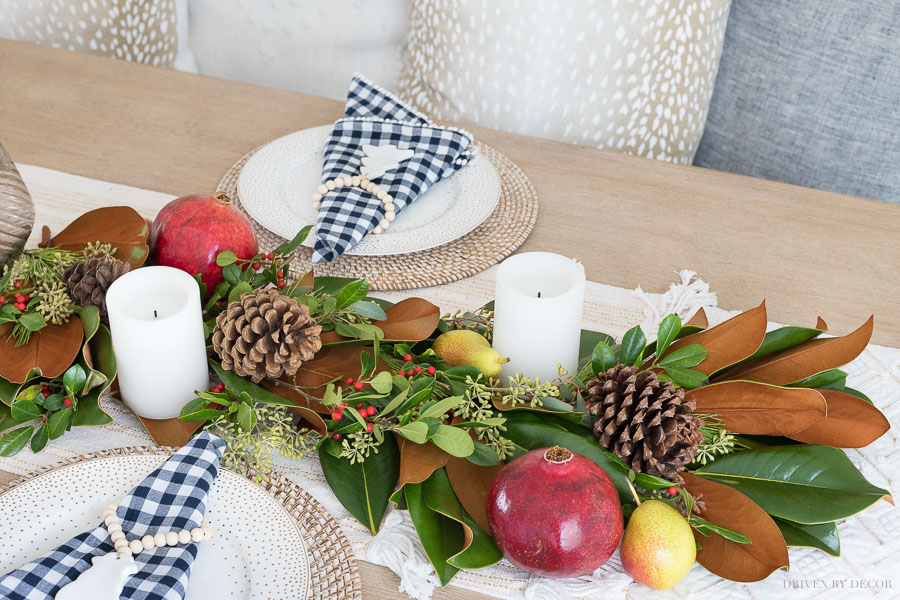 Fresh greenery table runner made with magnolia leaves, eucalyptus, berries, pinecones, pomegranates, and pears
