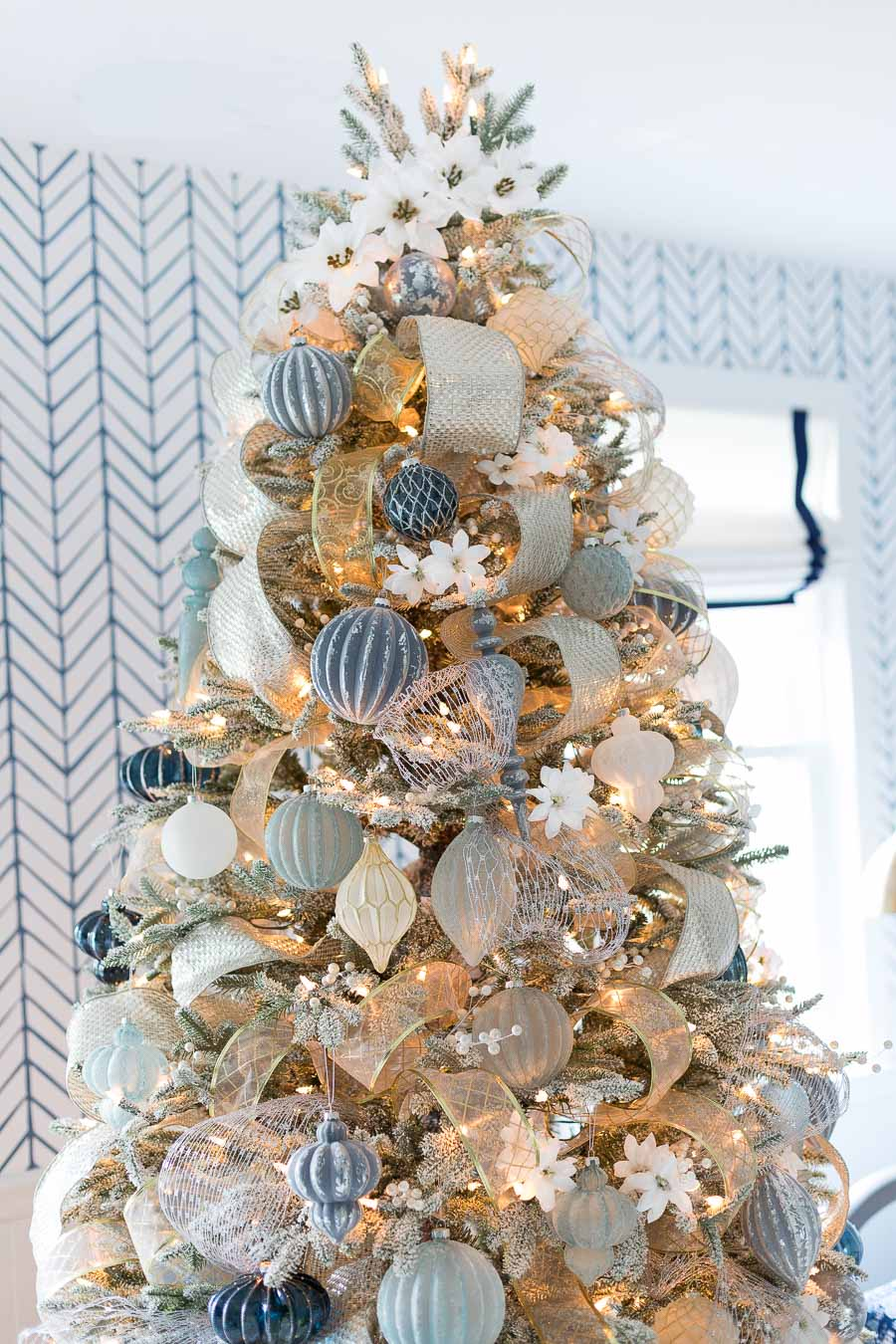 Faux white poinsettias spiral up the top of this gorgeous tree instead of a tree topper!