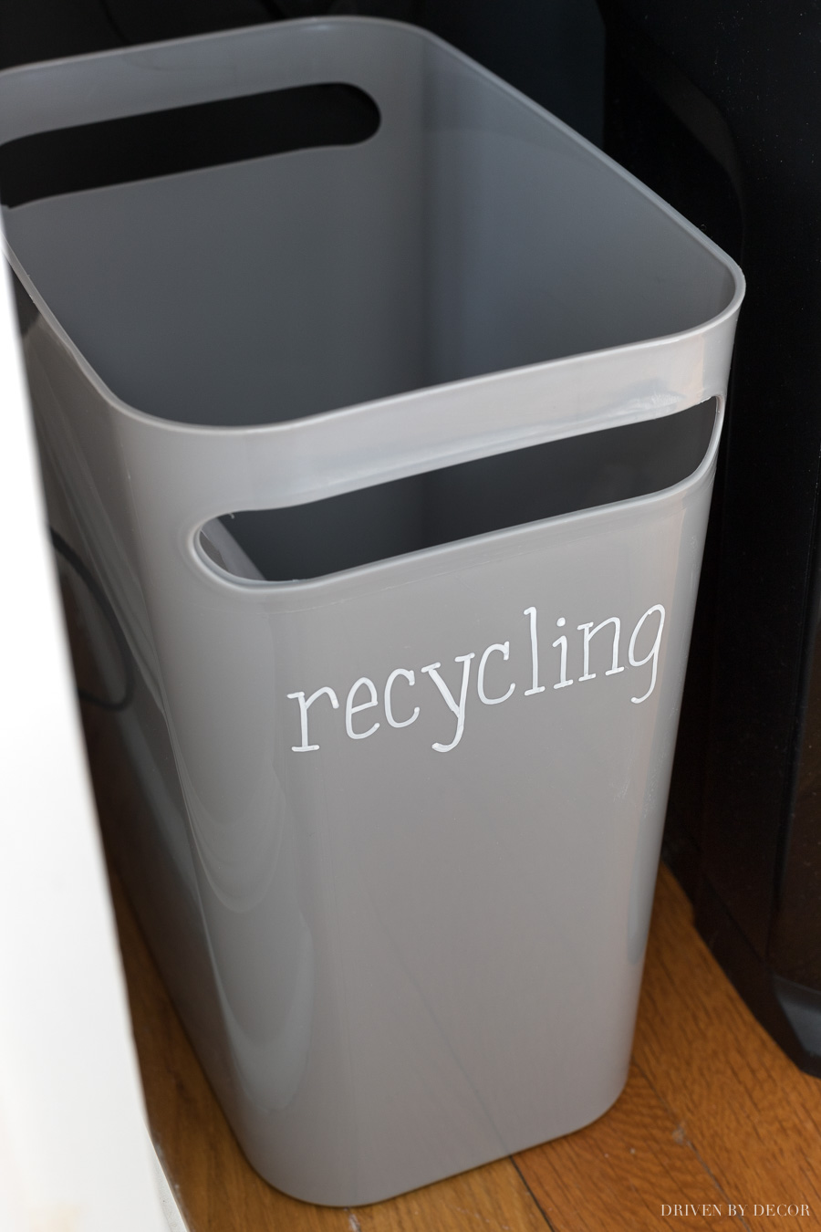 Slim gray trash can labeled for recycling with a chalk pen