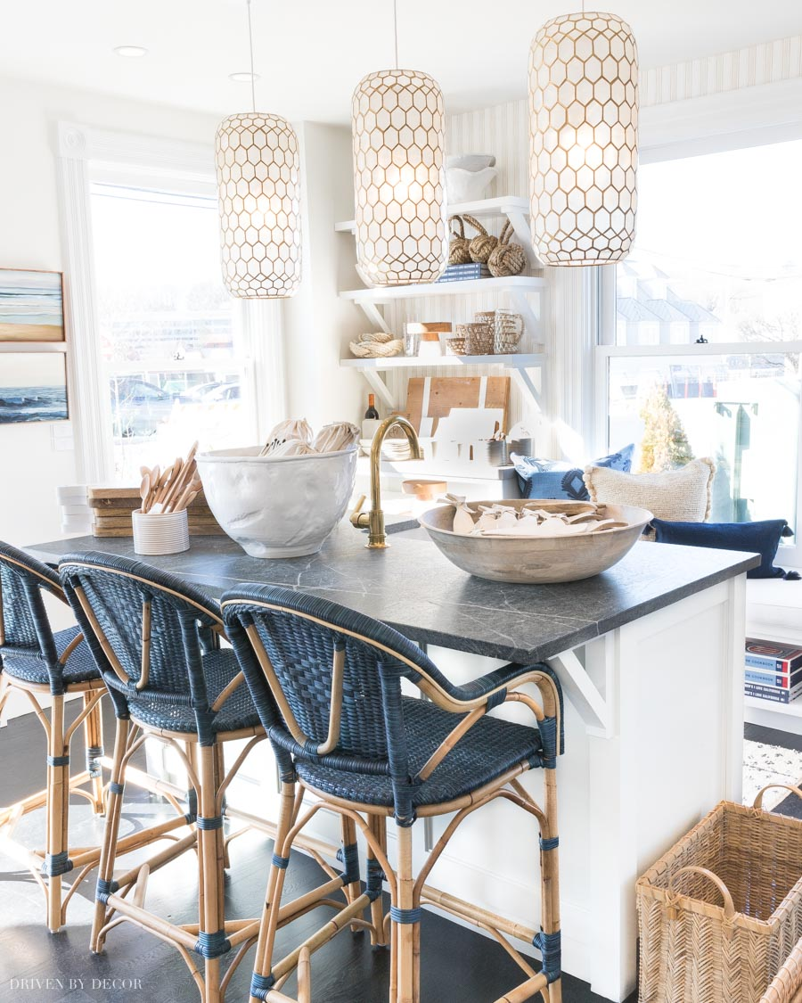 LOVE these blue woven counter stools at this kitchen island (and those pendants are gorgeous!)