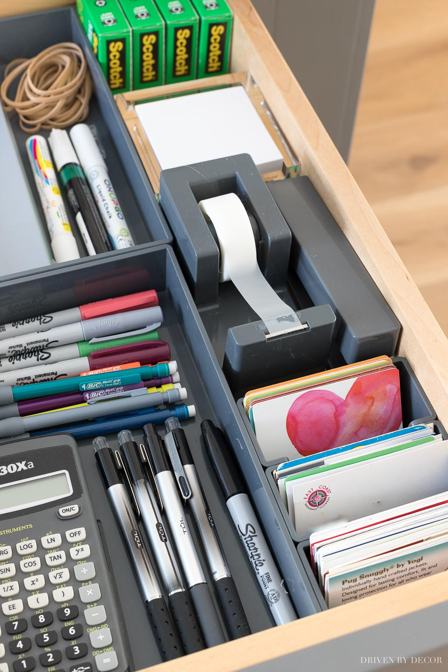A kitchen command center in a hidden drawer holding tape, stapler, and all sorts of other essentials!