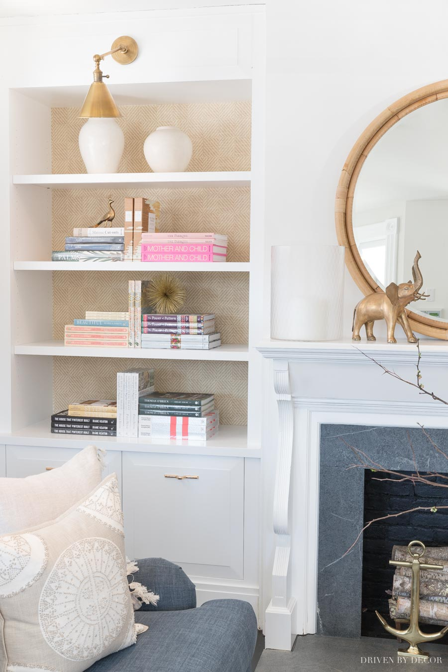Gorgeous grasscloth wallpaper on the back of the bookcase adds so much to this space!