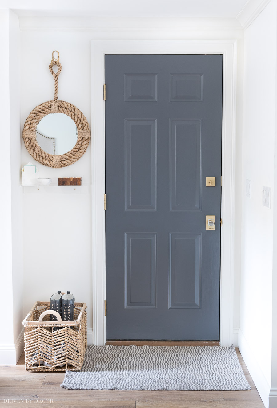 Love the small details of this garage entryway including the painted door, rug, mirror, and shelf!