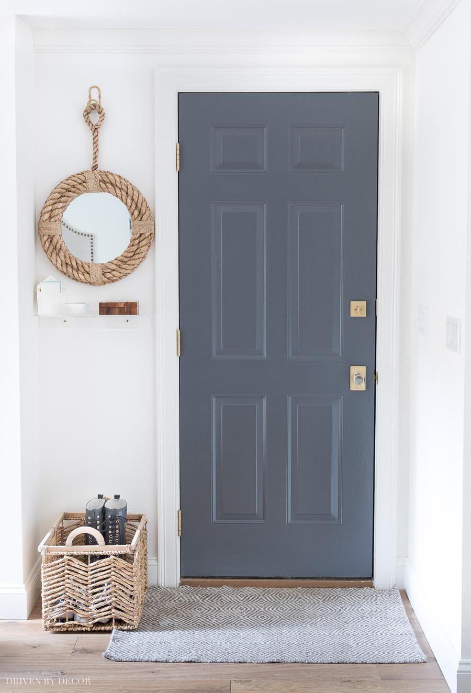 Lieben Sie die kleinen Details dieses Garageneingangs einschließlich der gemalten Tür, des Teppichs, des Spiegels und des Regals!