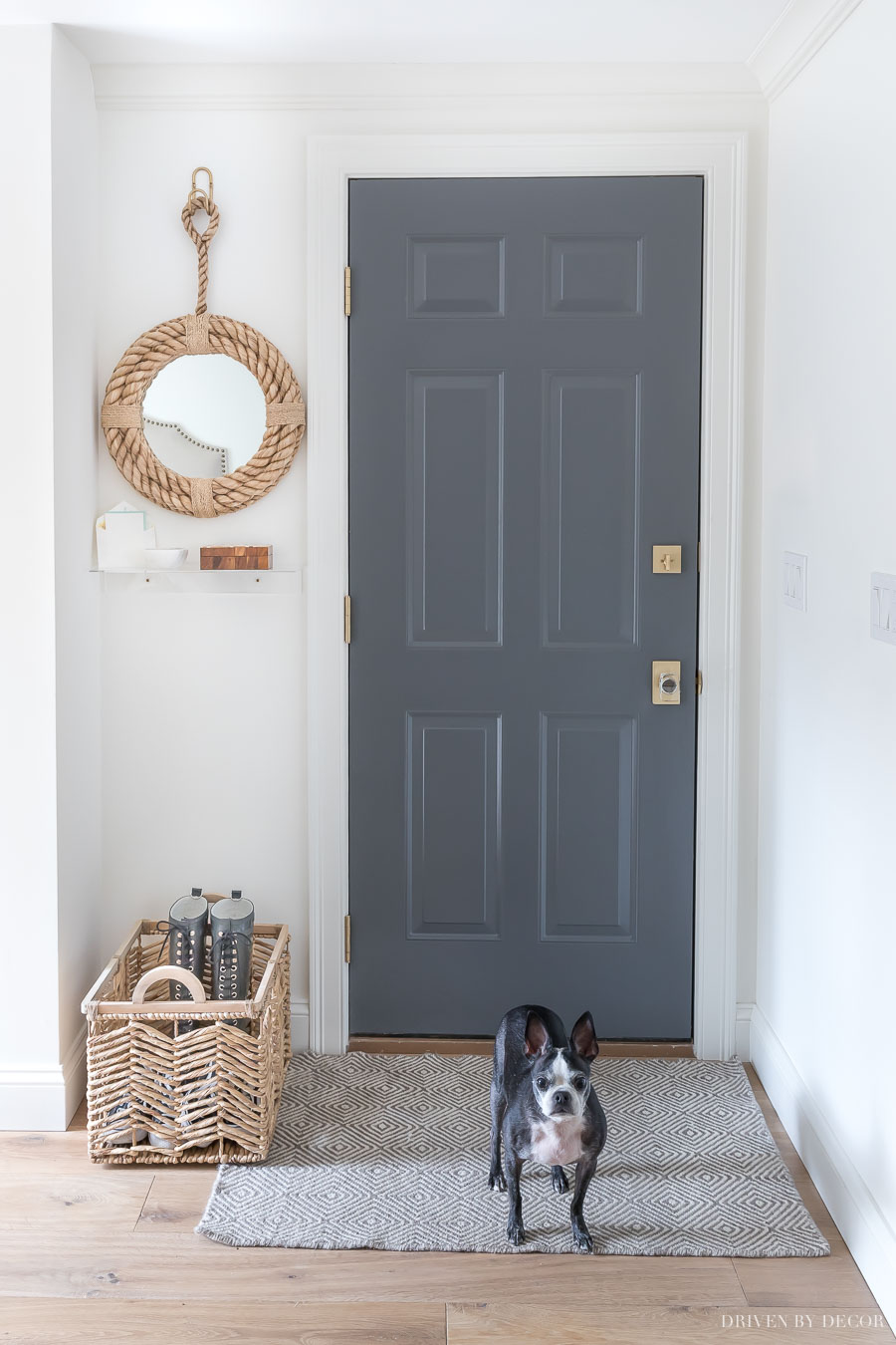 Such a cute small space entryway with rope mirror and shelf, rug, and basket for shoes!