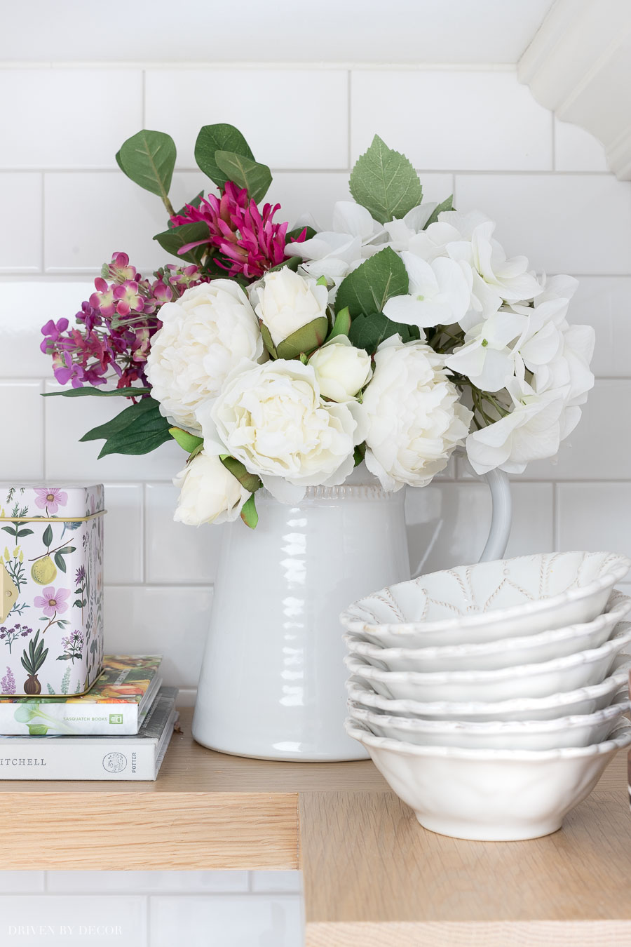 These realistic faux flowers in a pitcher are perfect for dressing up the look of your shelves!