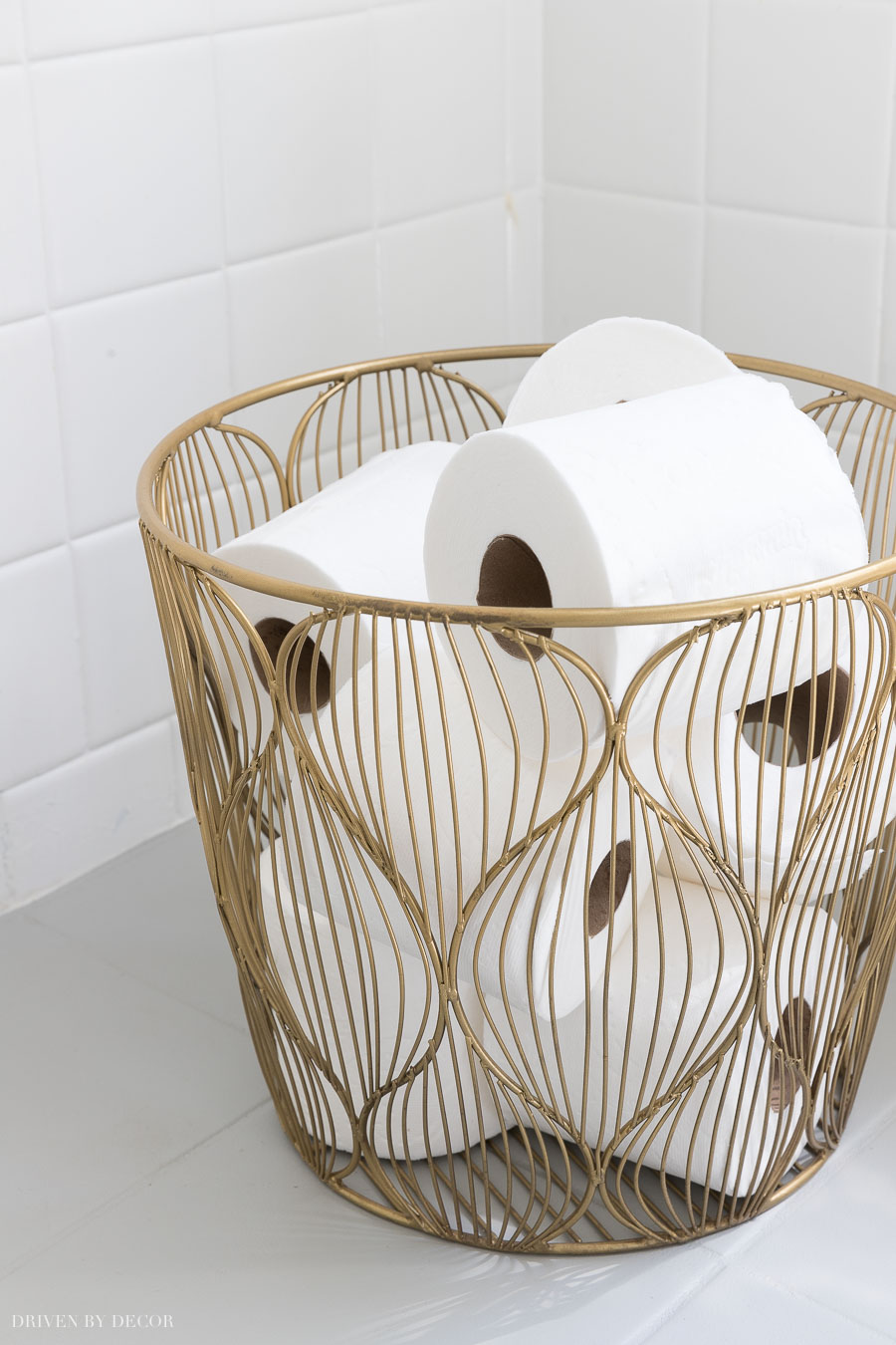 This small gold wire basket is perfect for holding extra rolls of toilet paper in the bathroom!