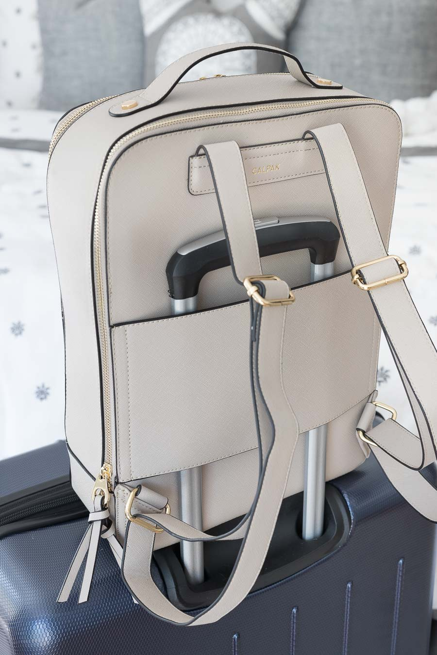 This travel backpack hooks onto the handle of your suitcase!