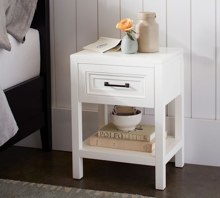 This small white nightstand is perfect for small spaces! Love the classic design with a drawer and shelf.