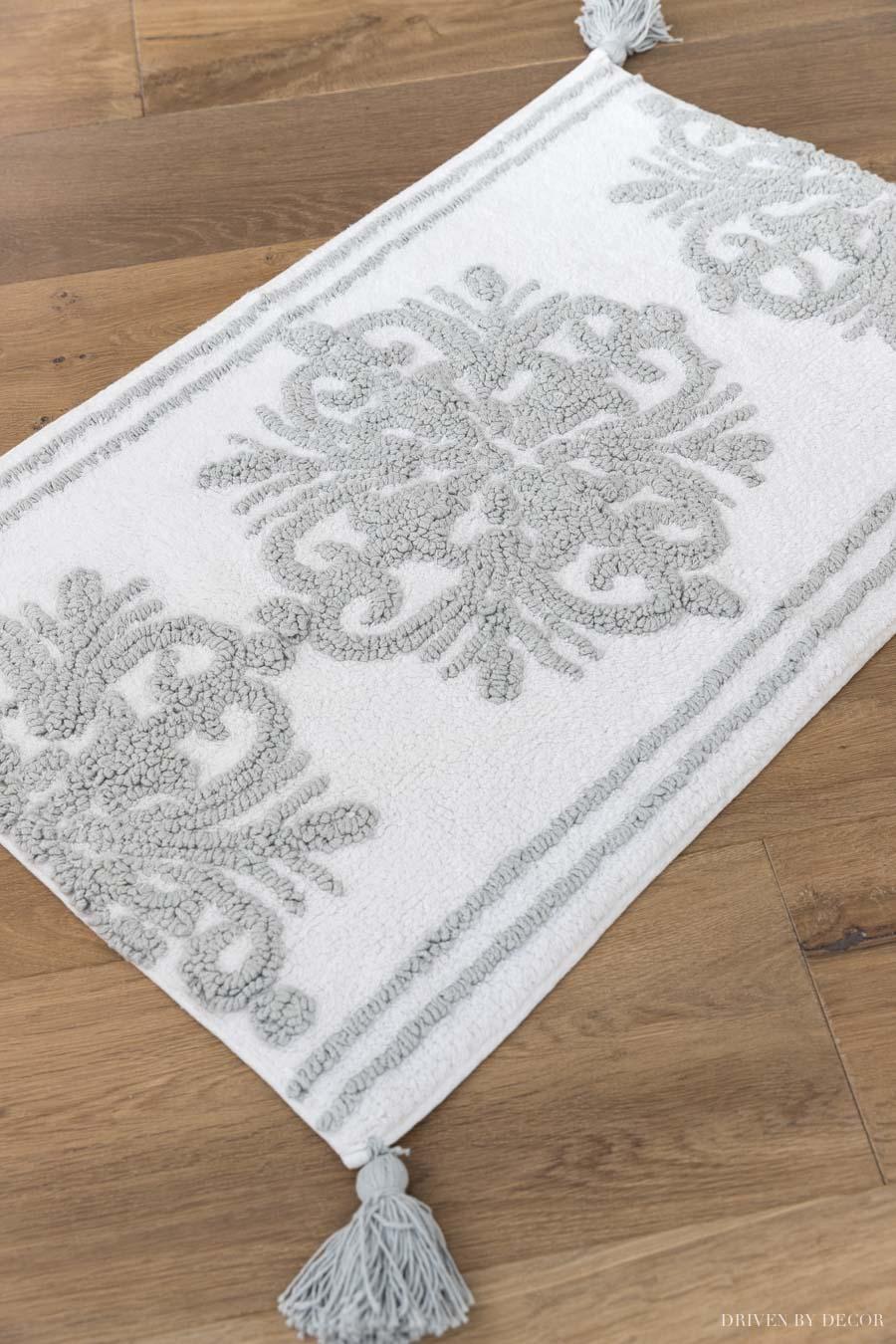 Beautiful gray and white bath mat with tasseled corners!