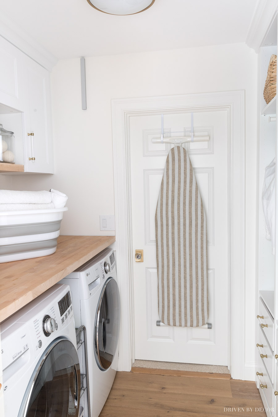 Free up space in your laundry room by hanging your ironing board on the back of the door!