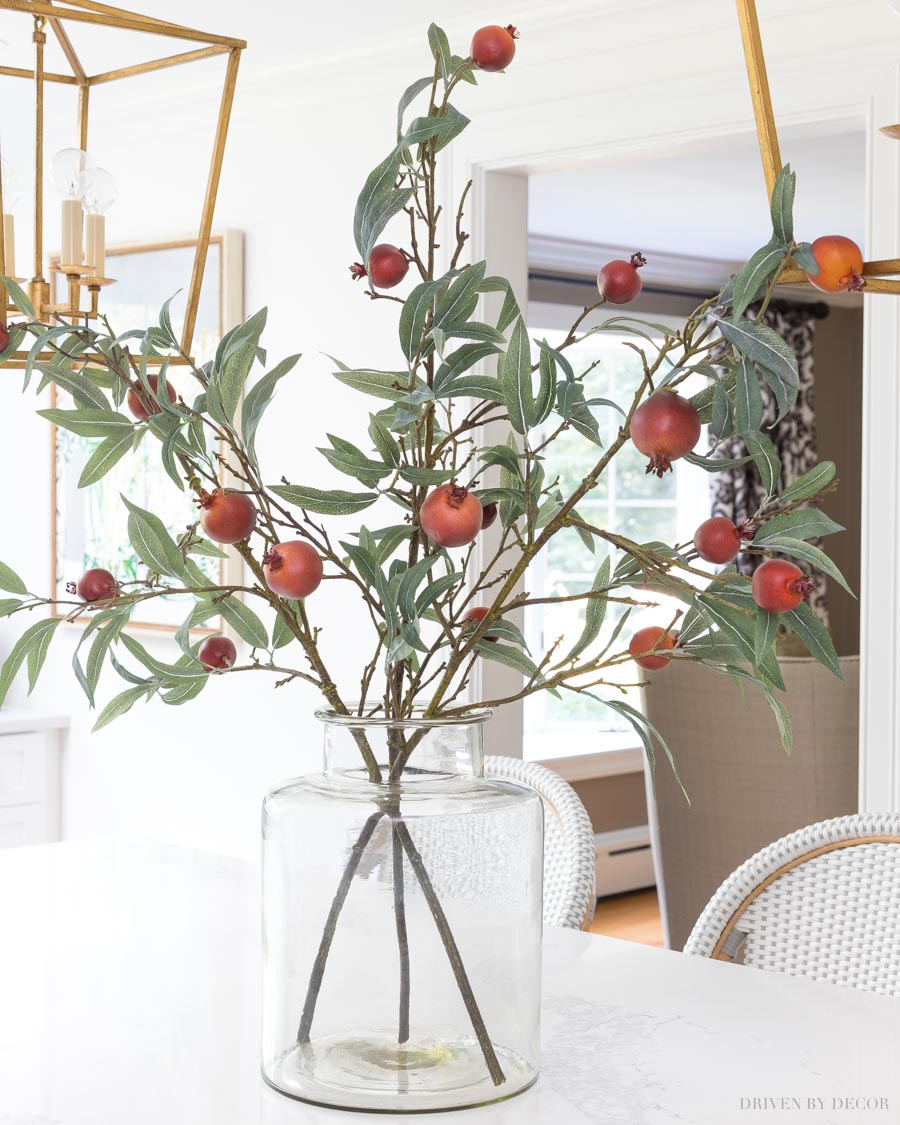 Love this simple but beautiful fall arrangement with faux pomegranate branches in a glass vase - sources linked in post!