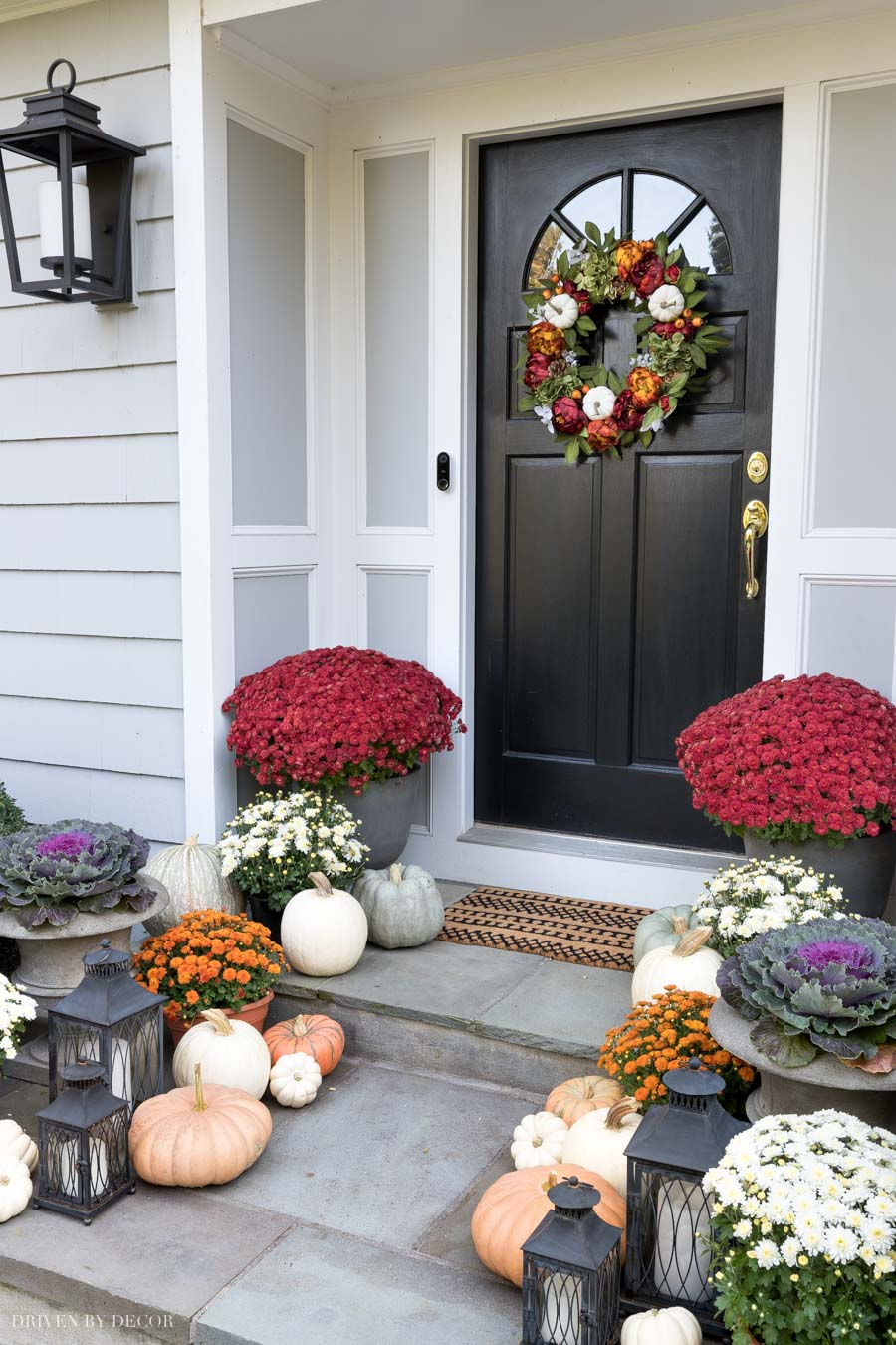 Mum, pumpkins, and lanterns line this gorgeous fall porch!
