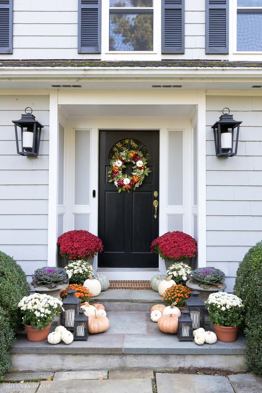 Love this look for a fall front porch! Pumpkins, mums, and lanterns line the steps!