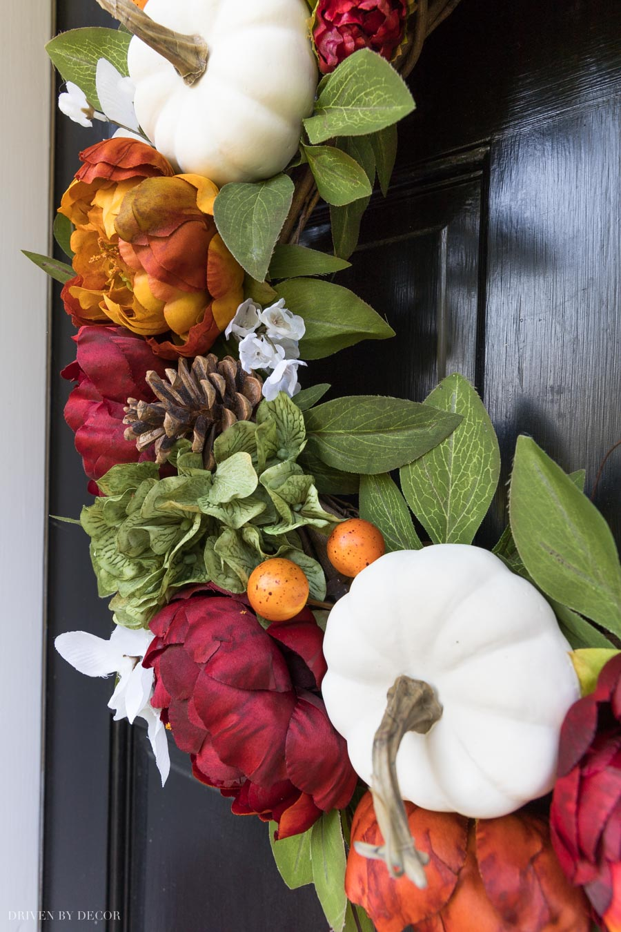 This fall wreath is a stunner! Filled with faux pumpkins, pinecones, and dark peonies!