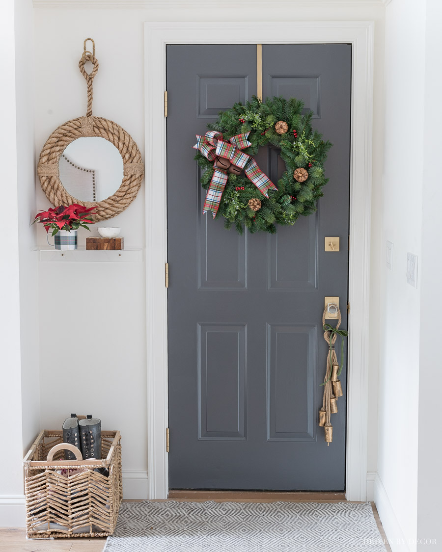A Christmas wreath with plaid bow and bells and bells on a rope door hanger are perfect for decorating the door we go in and out of every day!