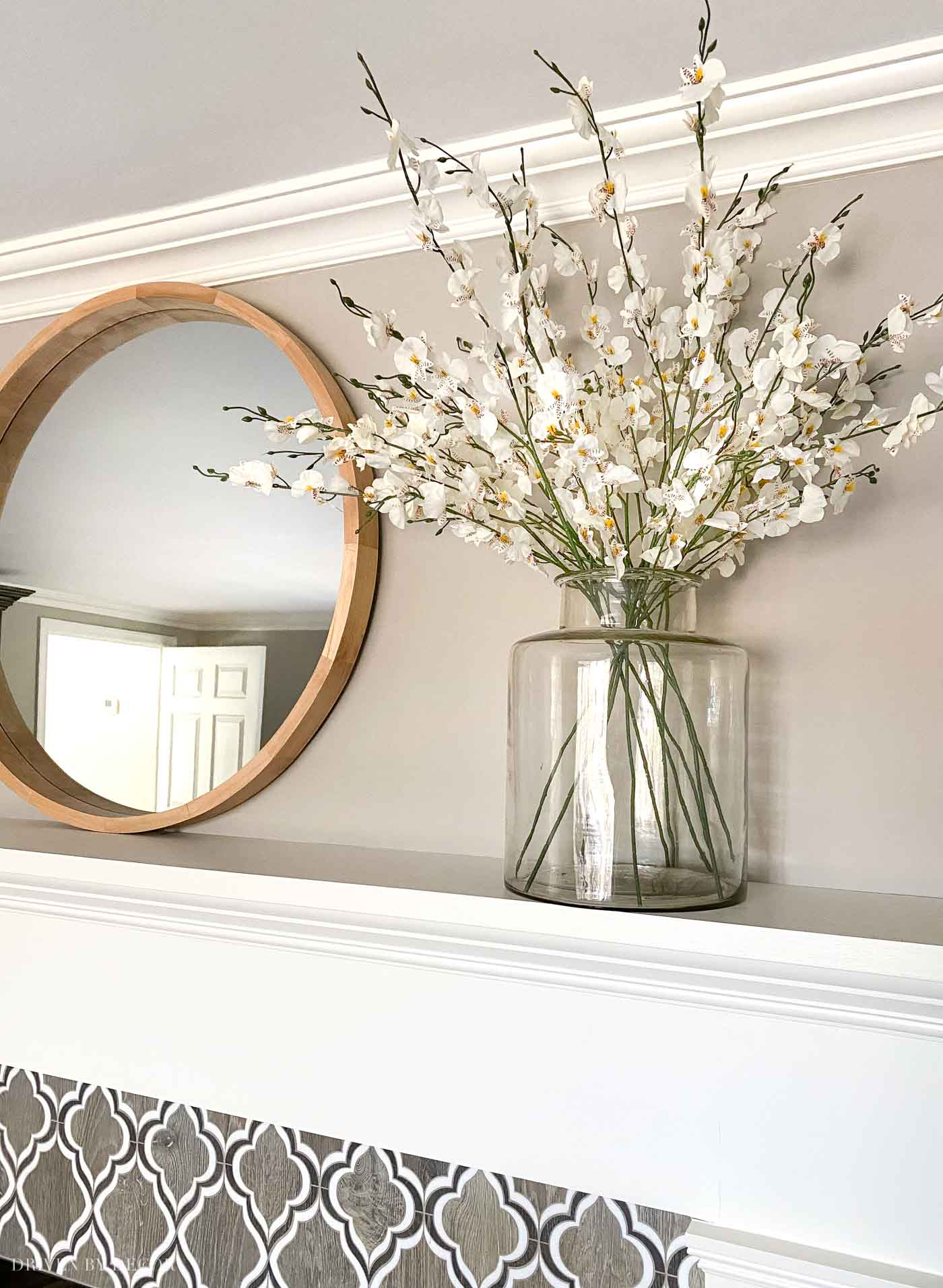 Love having a round mirror above the fireplace to reflect light around our room!