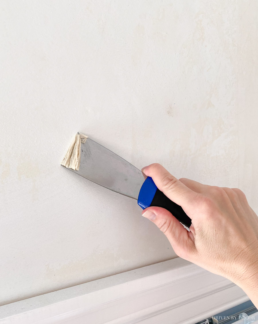 Using a putty knife to remove excess wallpaper glue
