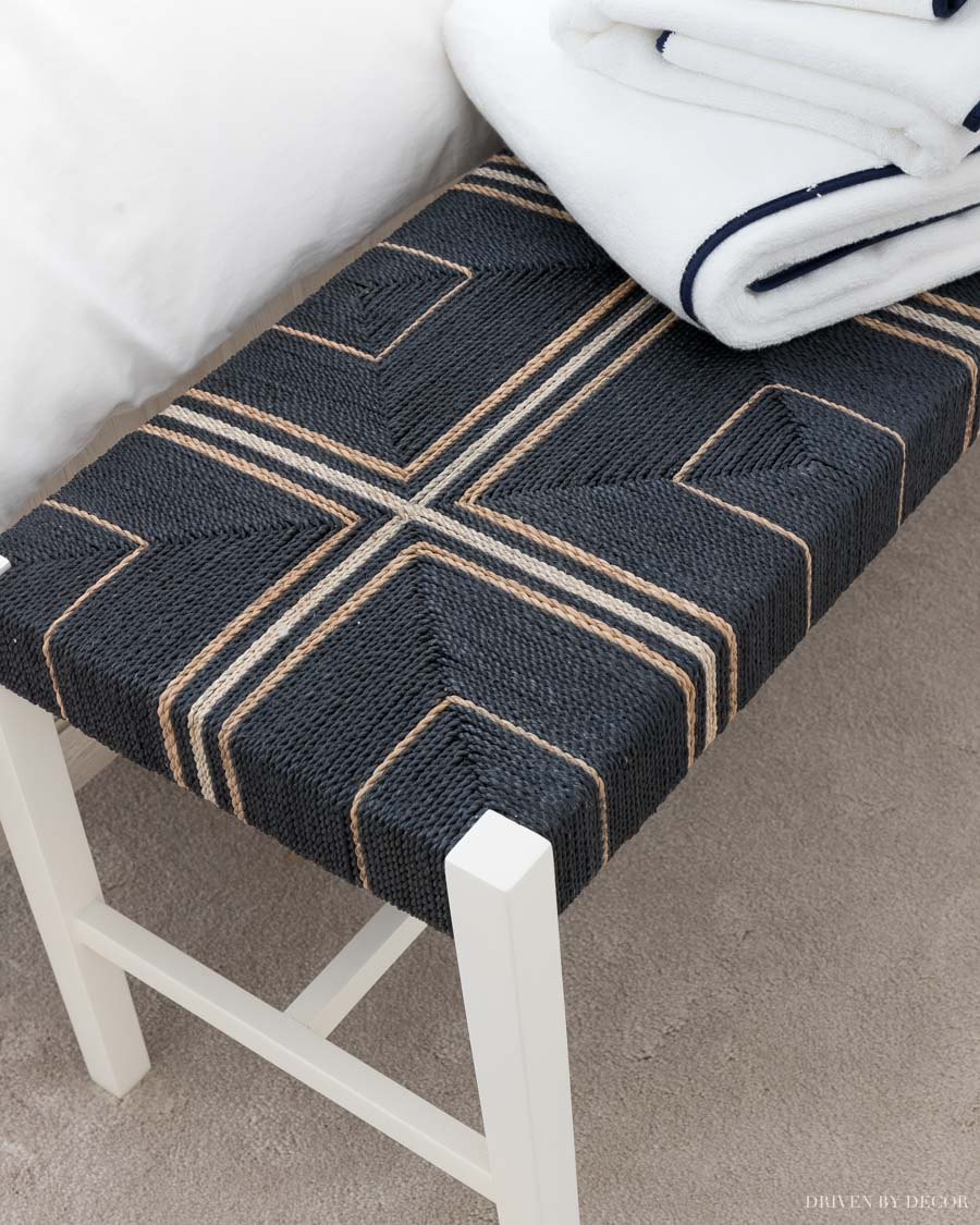 Gorgeous dark blue woven bench at the end of the bed