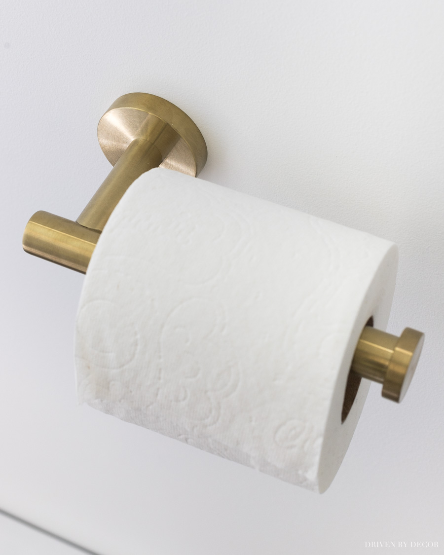 Beautiful but inexpensive brass toilet paper holder! Love all of her other bathroom decor ideas too!