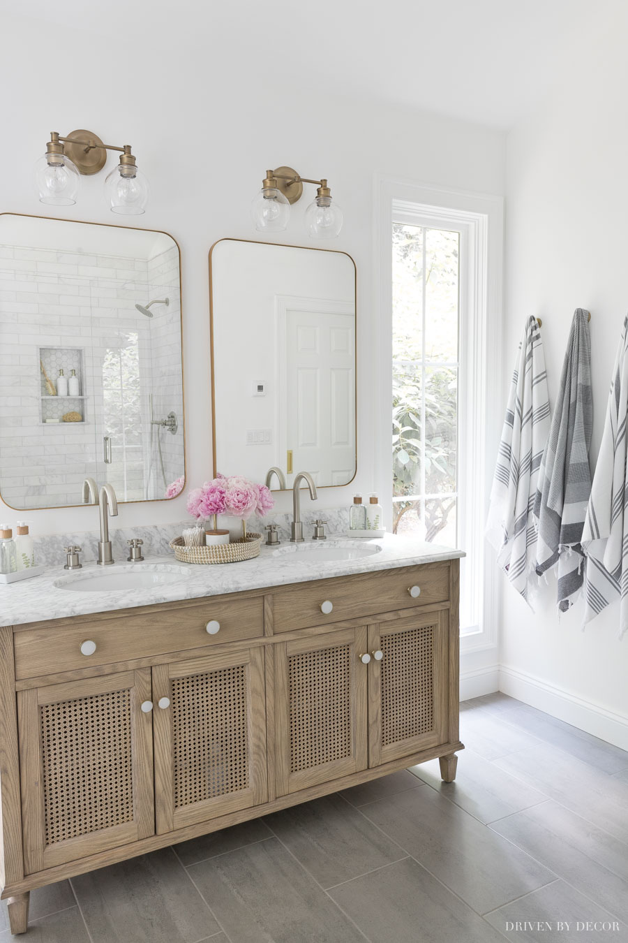 Love the layout of this double vanity between narrow windows and robe hooks on the wall for towels!