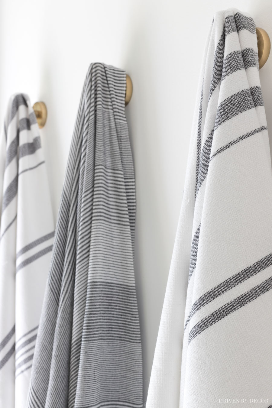 Loving the strriped towels on robe hooks in this bathroom!