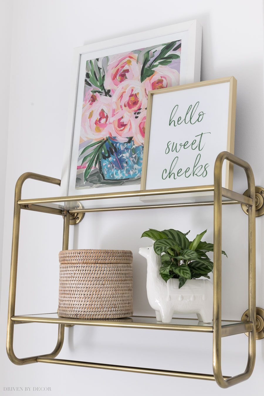 Love this brass wall shelf over the toilet