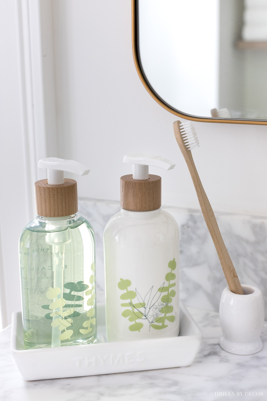 Soap and lotion pumps sit perfectly in this white tray by the bathroom sink. Love this simple toothbrush holder too!
