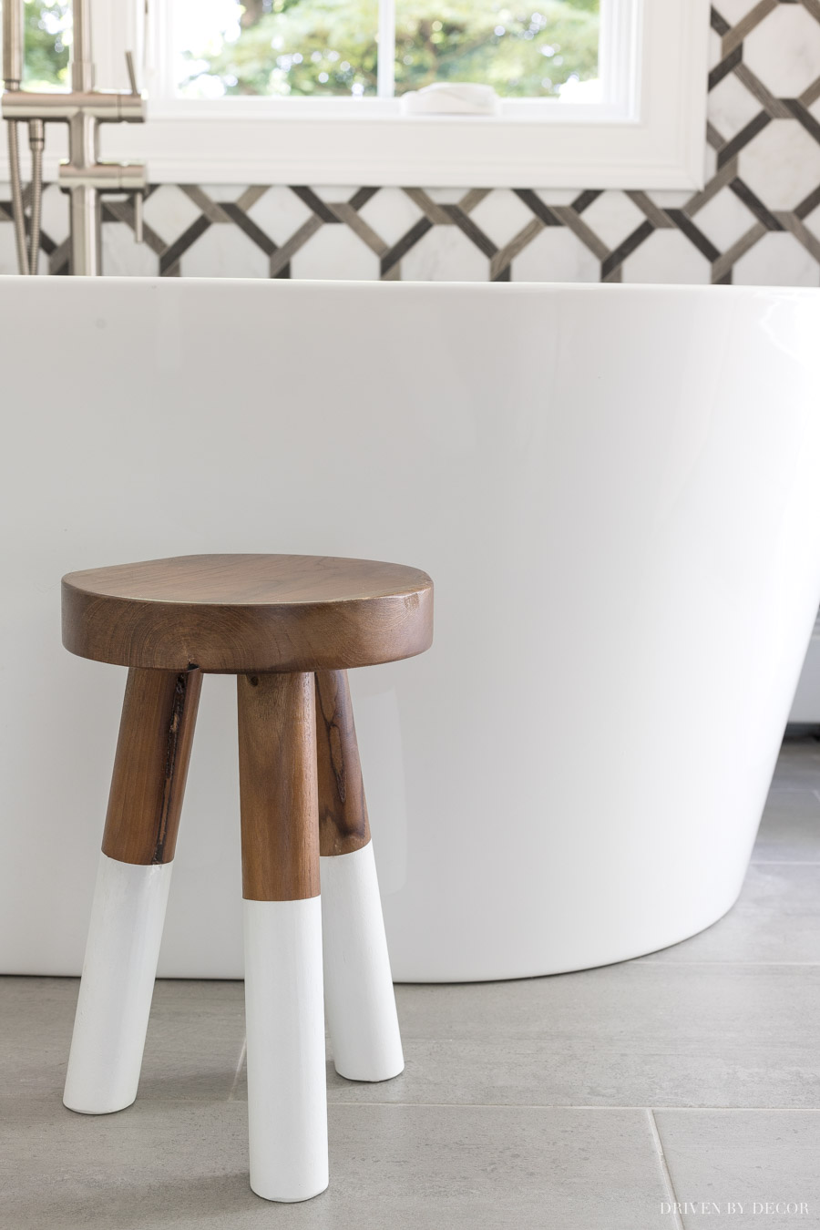 The cutest wood stool by the freestanding tub in this master bathroom