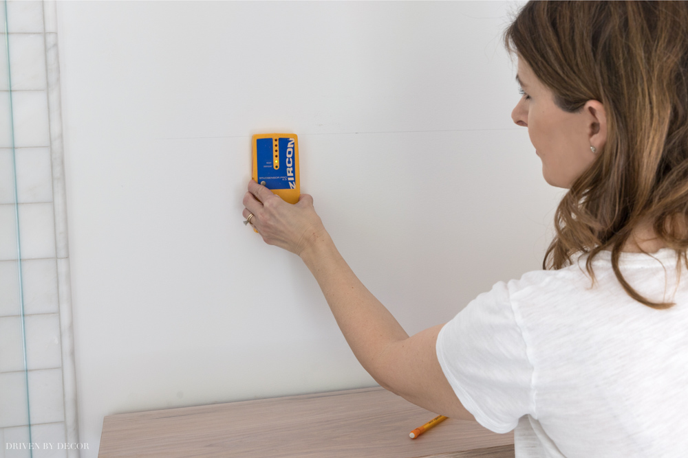 Using a stud finder to install our floating wood shelves