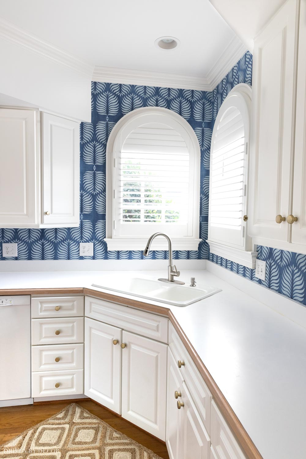 Adding a wallpaper backsplash to this kitchen made the white cabinets pop!