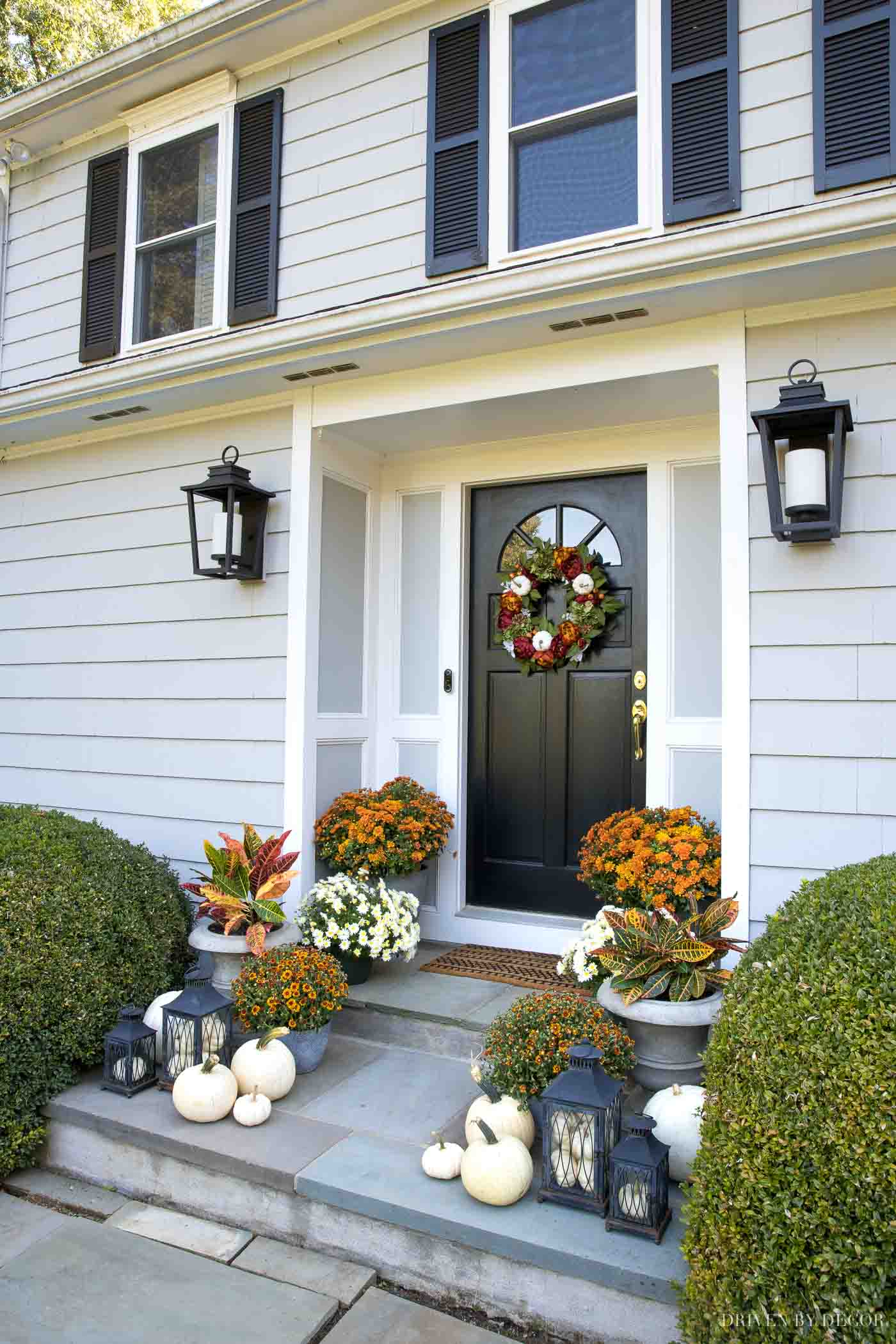All the details on our fall front porch decor including the pumpkins in our black lanterns, mums, beautiful fall wreath, and more!