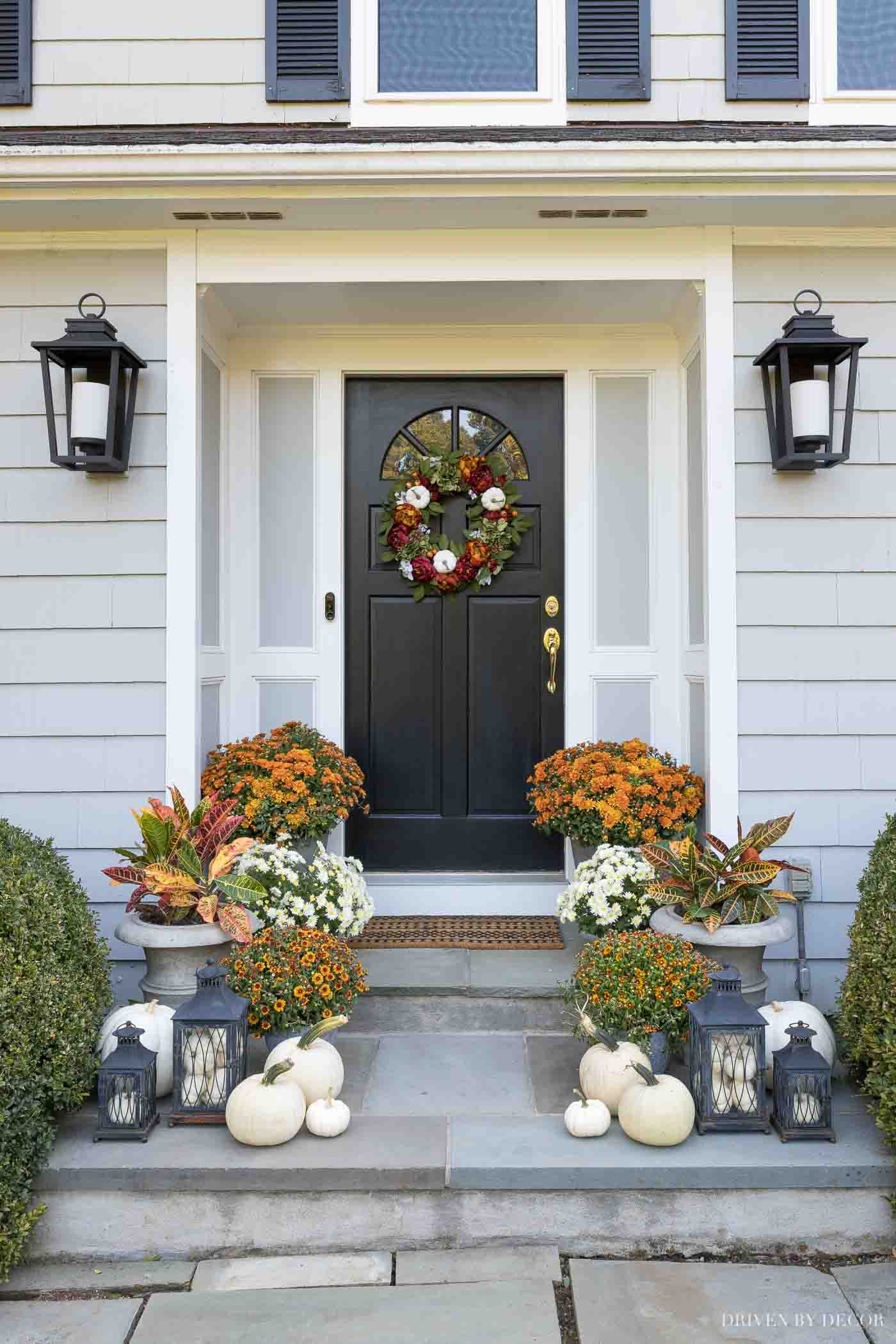 Our fall front porch decor with pumpkins, mums, lanterns, and crotons!