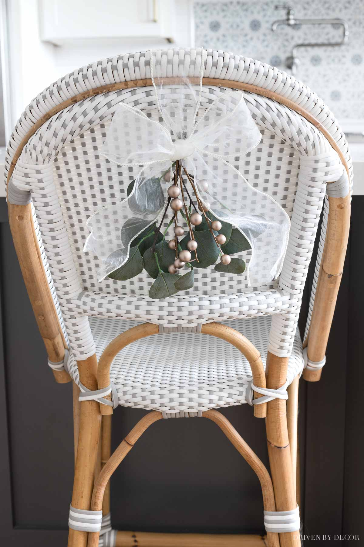 Mini greenery swags tied with a bow are the perfect simple Christmas decorations for the backs of our chairs