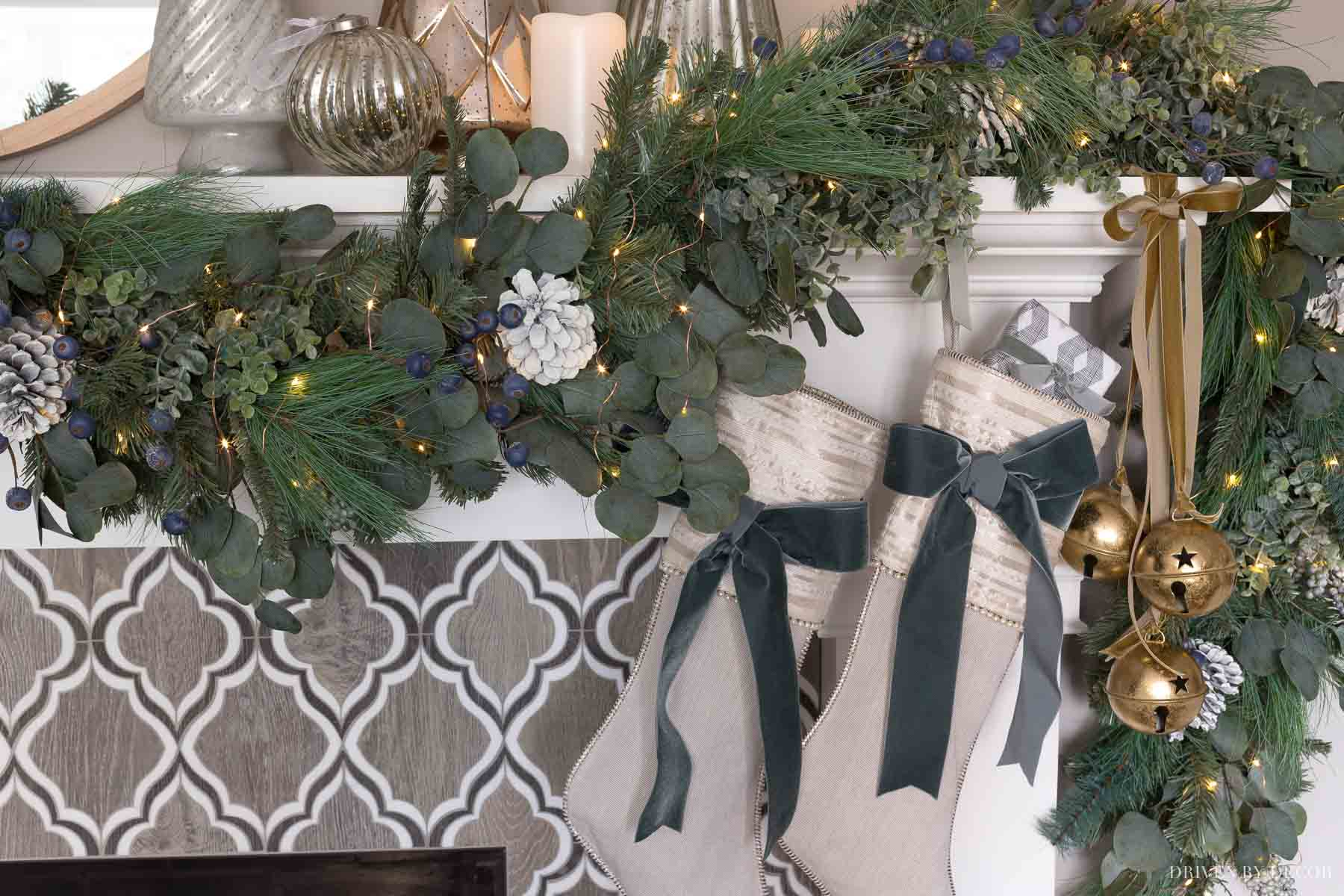 Our fireplace mantel decorated for Christmas with a greenery swag, stockings, jingle bells, and mercury glass trees
