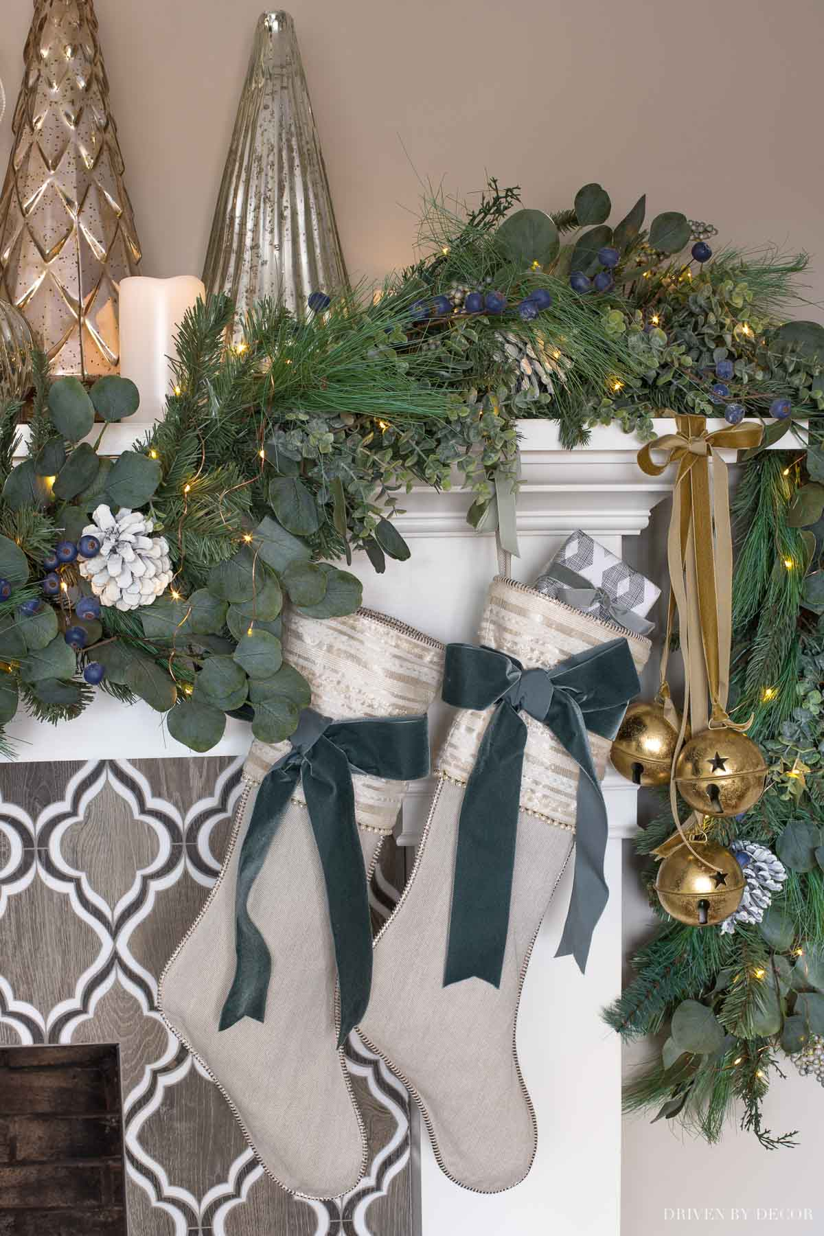 Large gold jingle bells tied with velvet ribbon on our fireplace mantel for Christmas