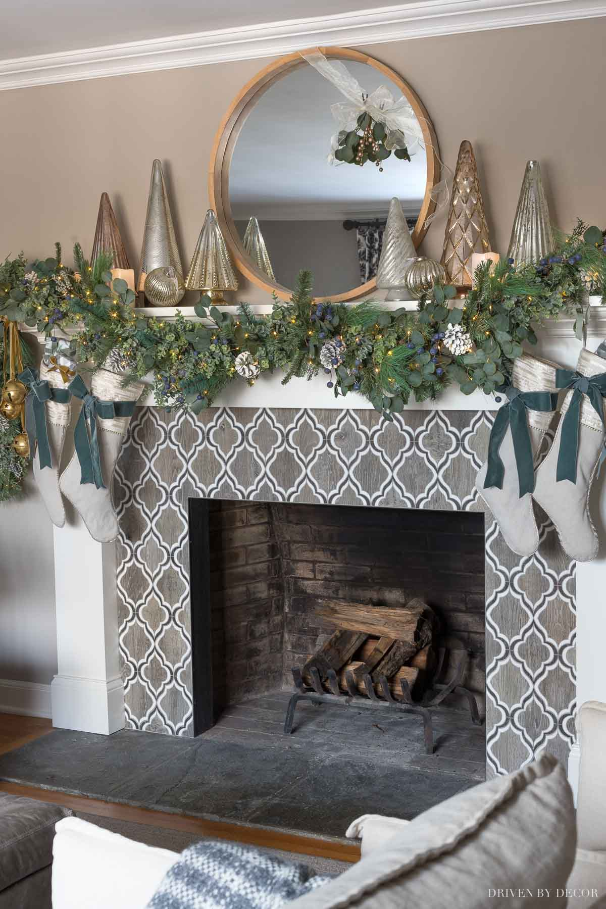 Our fireplace mantel at Christmas with greenery, mercury Christmas trees, glowing faux candles, and twinkle lights