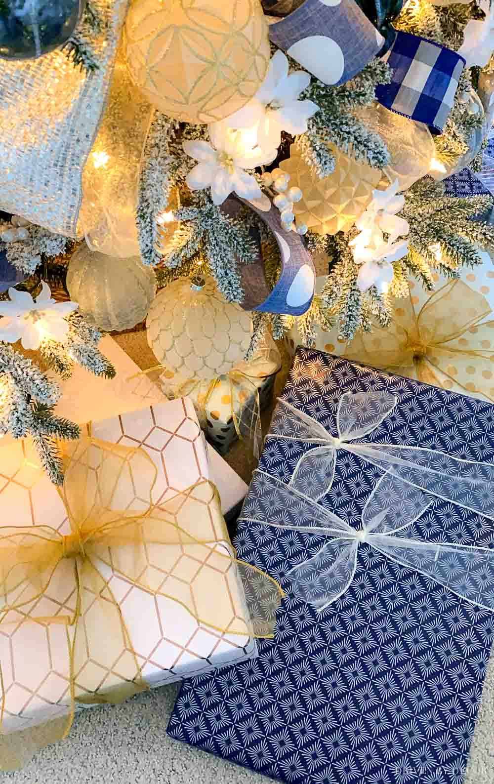 Packages wrapped in blue and white under the Christmas tree