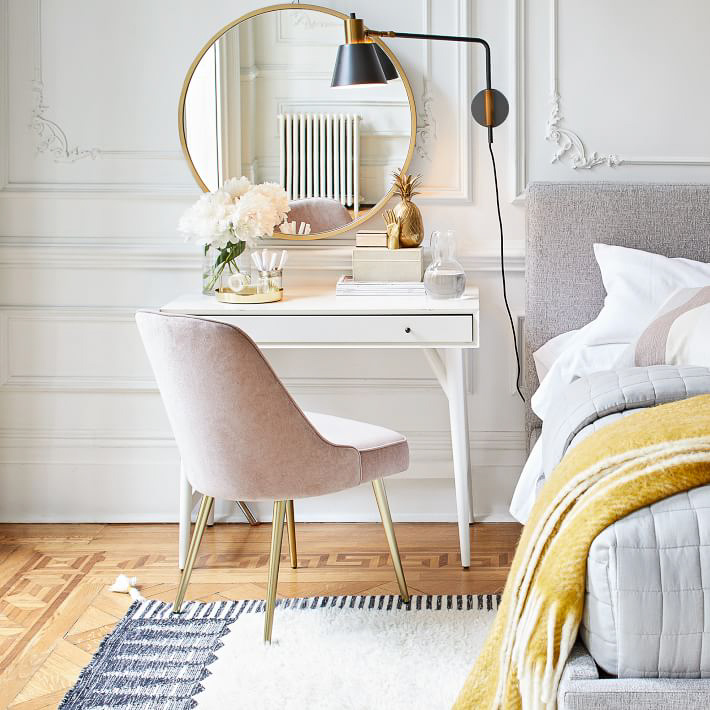 One 2021 design trend is double duty decor like this small desk that doubles as a nightstand