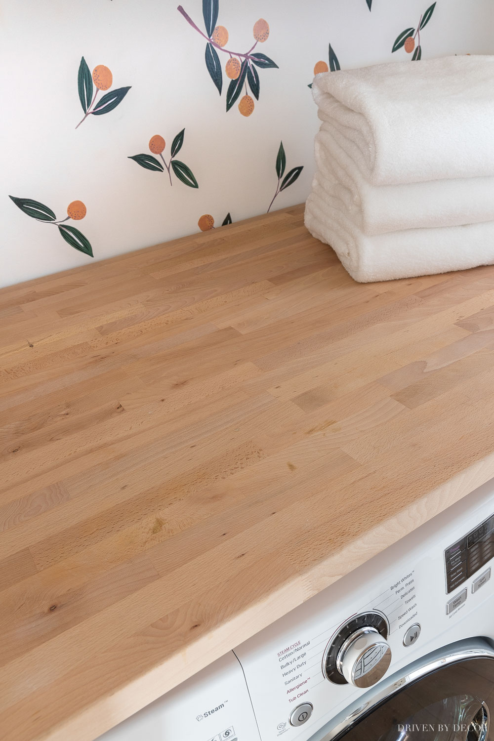 This Ikea wood countertop (butcher block) added a great space to fold and sort clothes in our laundry room!