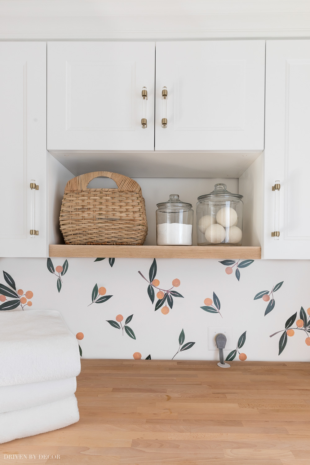 I added a wood shelf between the Ikea cabinets in our laundry room for open storage!