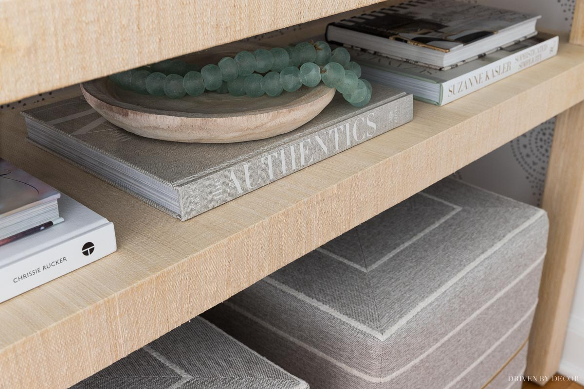 Entryway console table accessories - books, a shallow wood bowl, and glass beads