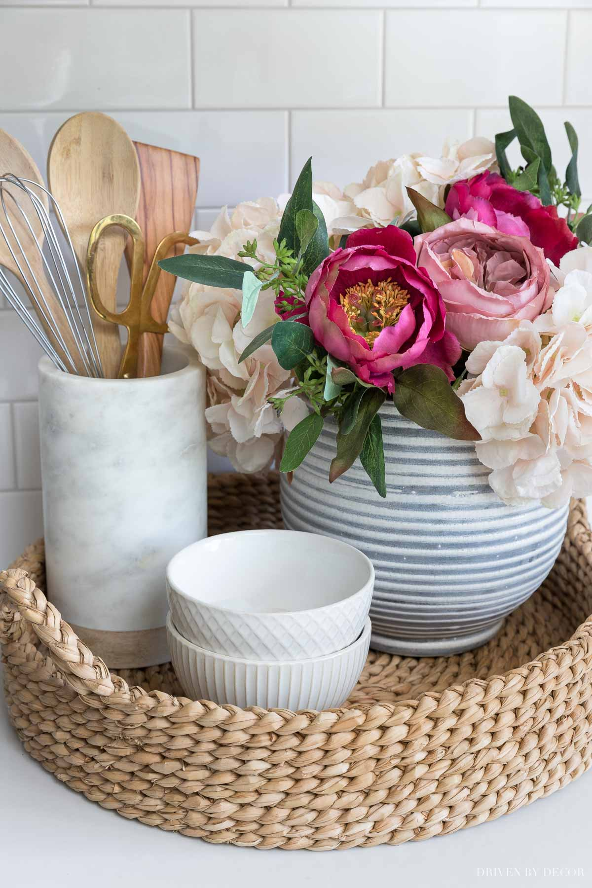 The artificial flowers in our kitchen sitting in a round woven tray