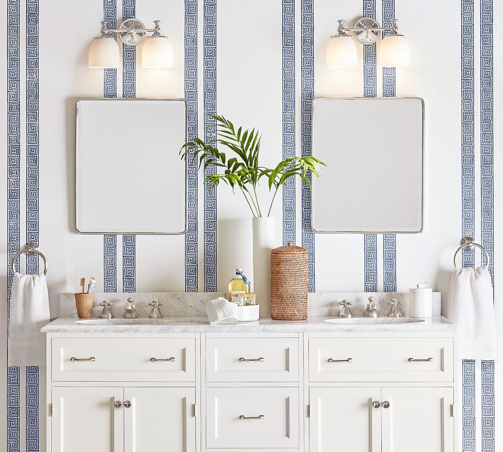 Simple rounded powder room mirrors on Greek key striped wallpaper