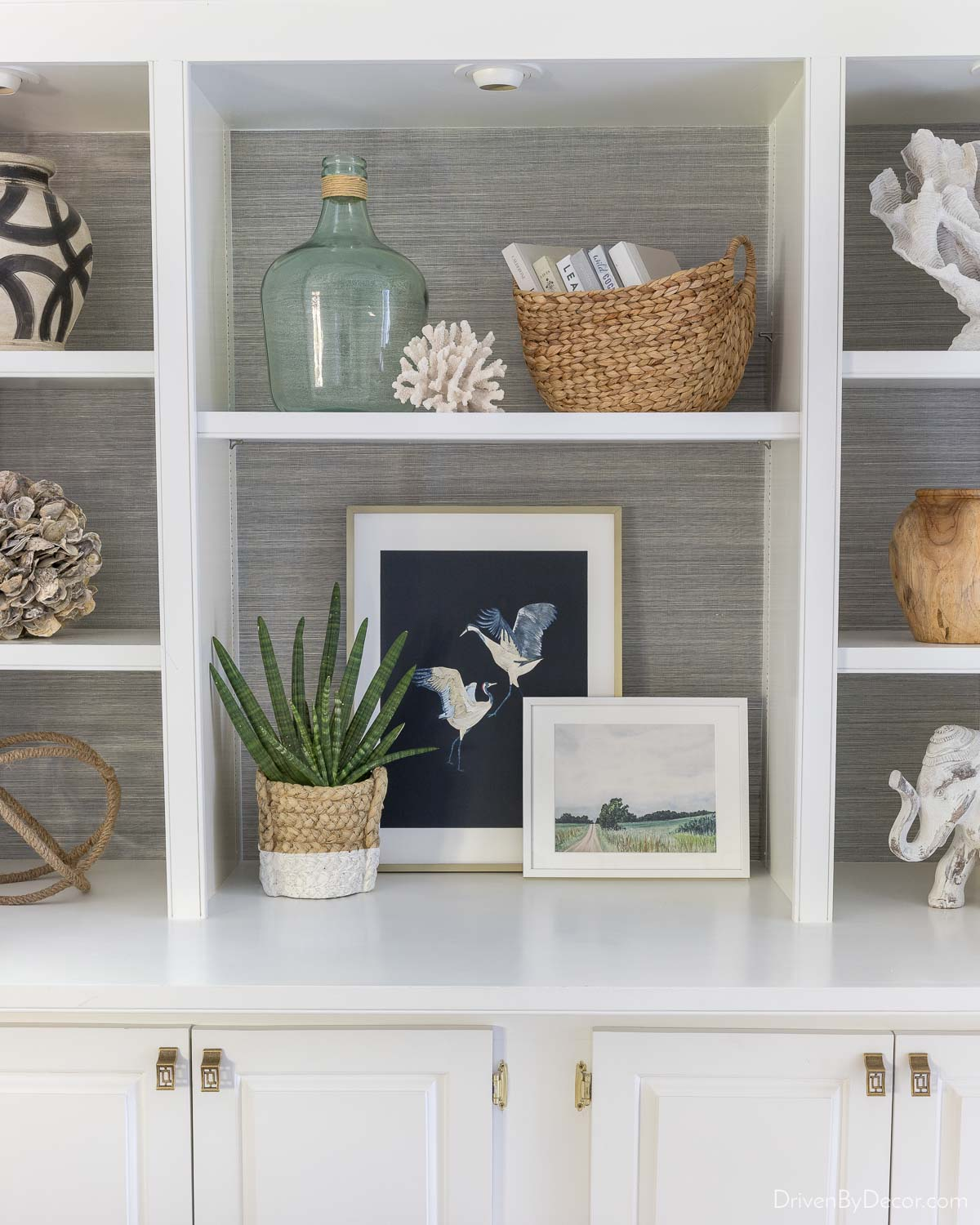 Charcoal grasscloth wallpaper makes the decor pieces on this bookcase pop!