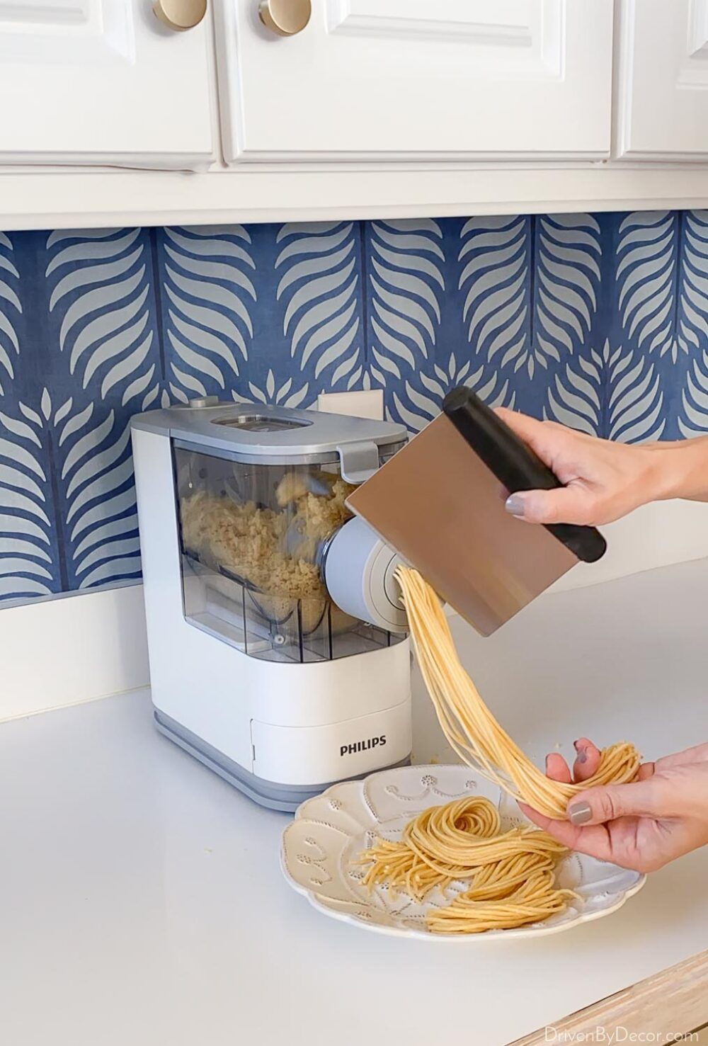 Cutting off the pasta as it comes out of the pasta making machine
